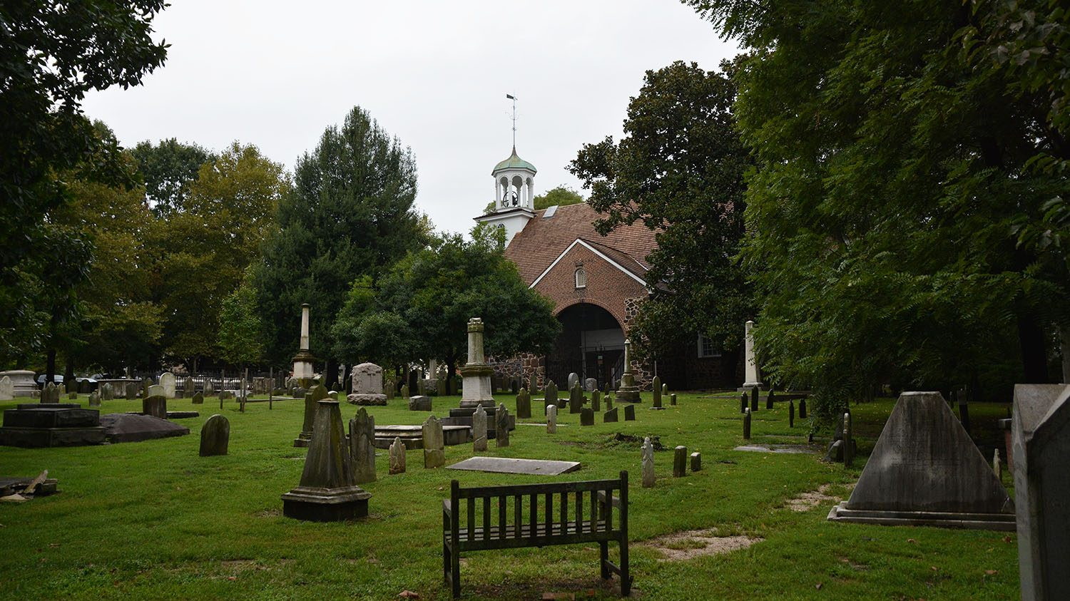 Old Swedes Church viewed from a distance, with many graves in the foreground.